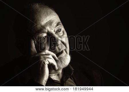 Portrait of a pensive old man over black background. Old age concept.