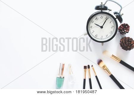 Female cosmetics and accessories with alarmclock on white background with copy space Flat lay