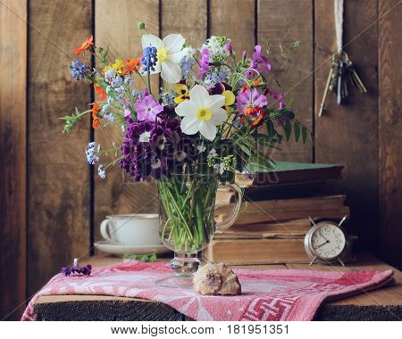 country still life with bouquet and old things: books alarm clock keys Cup. rustic style.