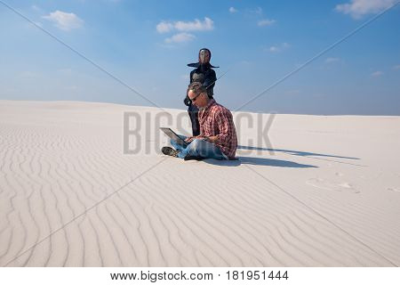 Man in stress sits with laptop in the middle of the desert and working hard samurai with a sword stands over him as an deadline symbol. Deadline concept - stress in freelance work.