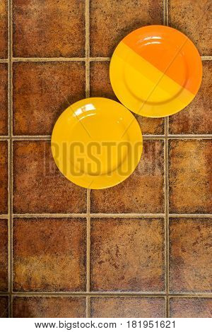 Two Multi-colored Plates In A Corner On A Brown Background