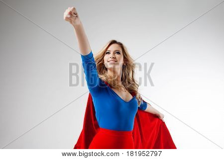 Superhero Woman. Young and beautiful blonde in the image of a super heroine in a red Cape