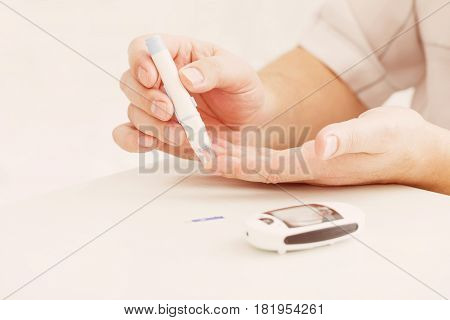 medicine diabetes glycemia health care and people concept - close up of male finger with test stripe