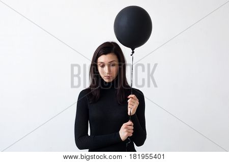 A sad girl holds a black balloon in her hands. She is sad for the loneliness and devastation of the soul