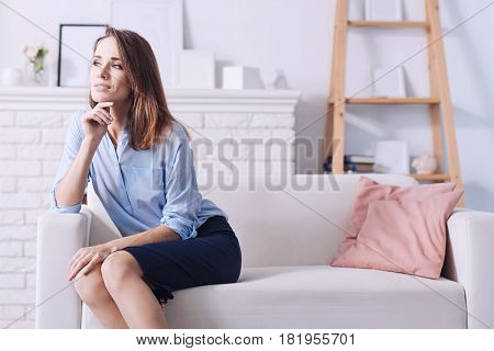 Successful woman. Beautiful self employed elegant businesswoman holding her chin and looking somewhere while sitting on the couch