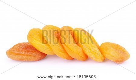 A heap of dried apricots on a white background with a light shadow viewed from above