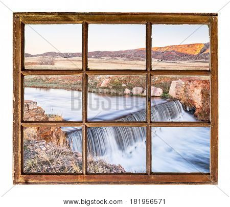a small creek dam at Colorado foothills as seen through vintage, grunge, sash window with dirty glass