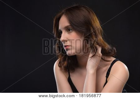 Portrait of wistful young brunette woman on black background
