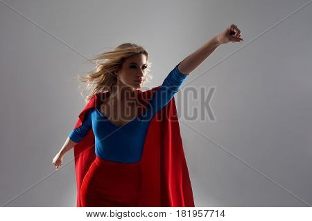 Superhero Woman. Young and beautiful blonde in the image of a superheroine in a red Cape growing