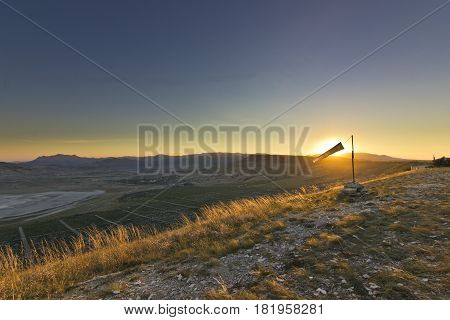 paraglider white windsock at sunset in mountains against sun