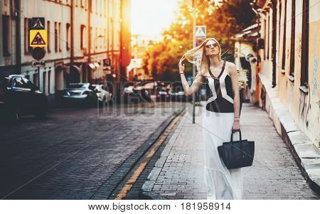 Attractive tall woman in long skirt with bag is fixing her hair while standing on street in the spring morning adult beautiful lady near city road with copy space for your advertising message