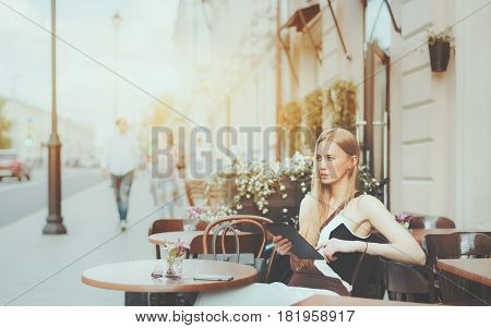 Charming caucasian woman is thoughtfully looking aside while sitting in street cafe with digital tablet attractive pensive blonde adult lady with touch pad is planing her day during morning breakfast