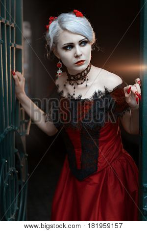 Woman peeks out of the gate she is in a red retro dress.