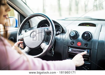 Woman Set Up Music In Car. Car Dashboard. Radio Closeup. Woman Sets Up Radio
