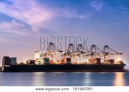 Cargo shipping and terminal unloading in twilight.