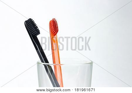 Closeup Of Two Toothbrushes In A Glass Beaker. For Men And Women. Full Black And Orange Brush. Brush