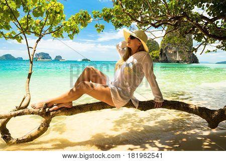 woman in straw hat resting tropical Thailand Railay beach