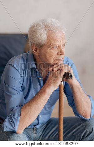 Old age. Nice grey haired pensive man sitting and leaning on the walking stick while being involved in his thoughts