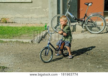 Tobolsk, Russia - August 11, 2007: Young boy on bicycle waiting near shop in old part of town
