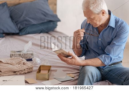 Nostalgic memories. Serious nice elderly man putting on his glasses and reading an old postcard while having nostalgic memories