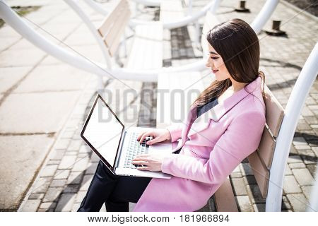Woman Sitting On The Bench In The Street With Laptop On Legs With White Screen Sunny Day Wearing In