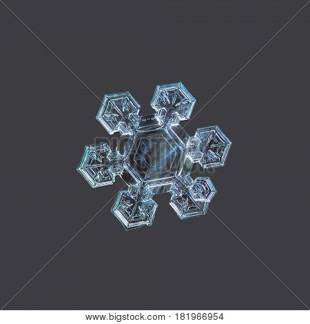 Macro photo of real snowflake: medium size snow crystal of star plate type with six short, broad arms with complex pattern and big, flat central hexagon with simple inner pattern. Snowflake isolated on uniform dark gray background.