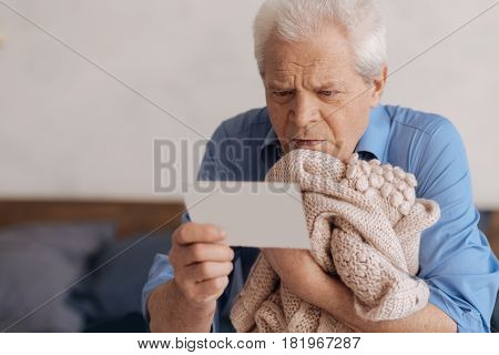Message for my husband. Sad unhappy senior man holding his wifes knitted jacked and reading a note while having nostalgic memories