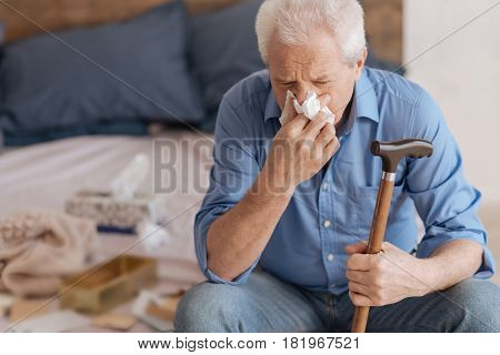 In grief. Unhappy depressed senior man holding a walking stick and using a paper tissue while crying