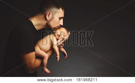 Newborn baby in his father's hands in the dark on a black background