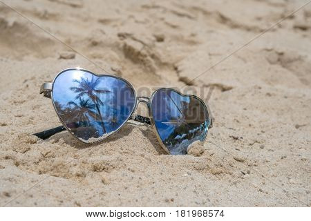 Sunglasses heart shape on the tropical beach sand