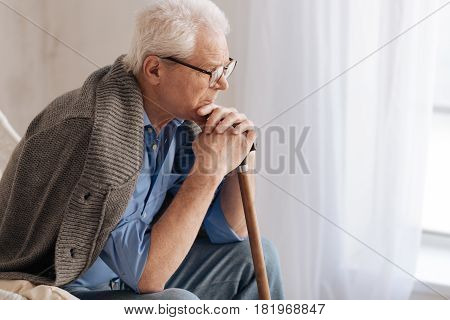 What is life. Gloomy unhappy elderly wan leaning on the walking stick and thinking about life while being depressed