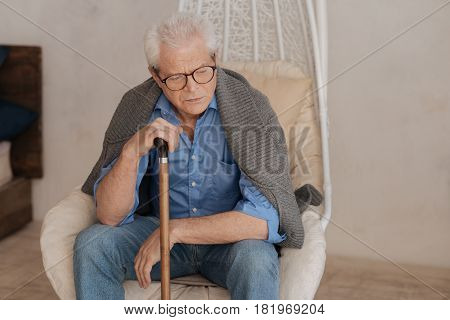 I am exhausted. Moody sad unhappy man leaning on his walking stick and thinking about his past while resting in the armchair