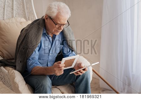 Pictures from the past. Sad gloomy unhappy man sitting in the armchair and holding old photos while remembering his youth