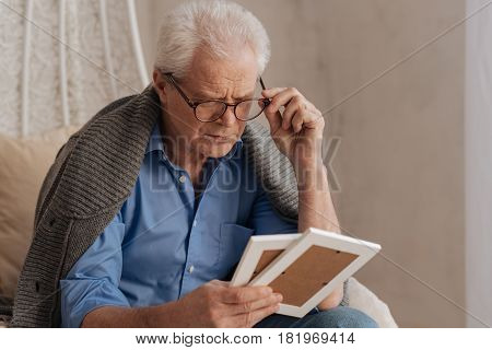 Important people. Sad pessimistic senior man fixing his glasses and looking at the photograph while holding them