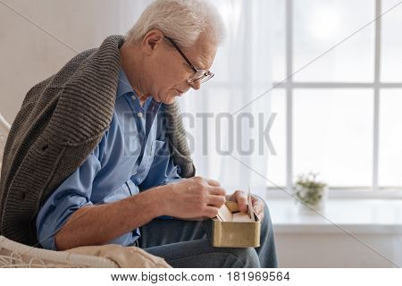 I am lonely. Depressed pessimistic aged man sitting on the bed and turning over old letter while having nostalgic feelings