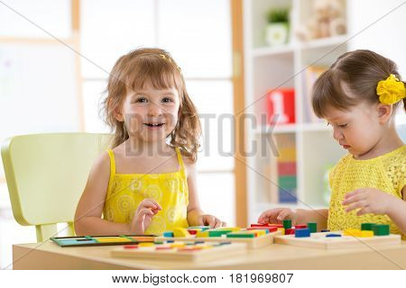 Children kids play with educational toys, arranging and sorting colors and shapes. Learning through experience conception.