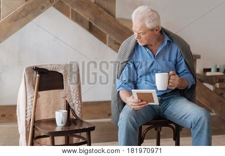 It is empty. Gloomy aged man looking at the empty chair near him and remembering his wife while holding her photo