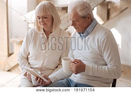 Close person is gone. Unhappy sad elderly couple looking at the photo and being sad about it while sitting together