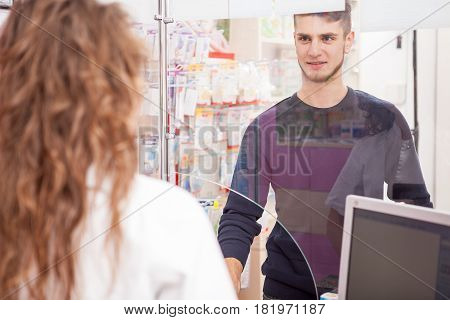 Pharmacist woman and a client in front of the shop. Healthcare business
