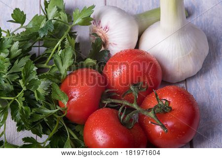 fresh tomatoes garlic and frizzy parsley on a wooden table
