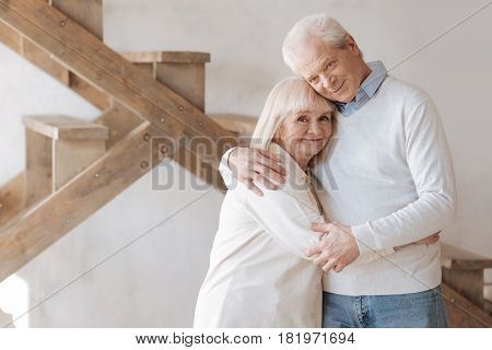 Care and love. Delighted positive aged couple standing together and hugging each other while expressing their feelings