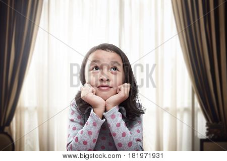 Beautiful Little Asian Girl Thinking And Daydreaming At Living Room