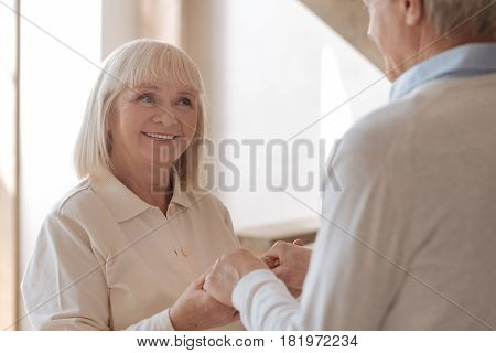 Happy together. Happy joyful nice woman looking at her husband and smiling while holding his hands