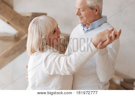 Do you remember this song. Cheerful nice elderly woman holding the hand of her husband and smiling while dancing with him