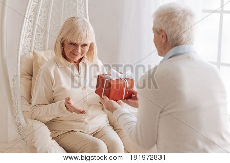 Happy birthday. Nice caring aged husband holding a gift box and giving his wife a present while celebrating her birthday
