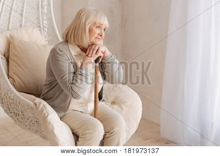 Bad mood. Sad unhappy aged woman sitting in the armchair and leaning on the walking stick while thinking about her problems