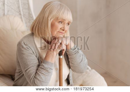 Sad thoughts. Unhappy depressed elderly woman leaning on her walking stick and being involved in thoughts while sitting in the armchair