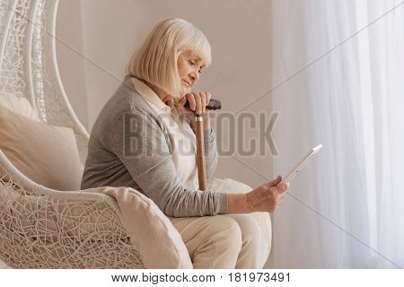 Sad memories. Moody depressed aged woman holding a photo and looking at while sitting in the armchair