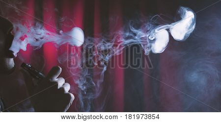 Young Man Vaping Clouds On A Dark Background.