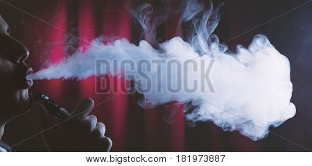 Holding Electronic Cigarette Or E Cig And Vaping Clouds.
